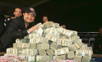 Yang of Temecula, California poses with a pile of cash after winning the World Series of Poker main event at the Rio Hotel and Casino in Las Vegas