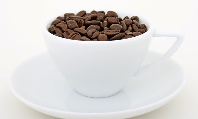 Cup of coffee beans, isolated on white, macro closeup, close-up with copy space